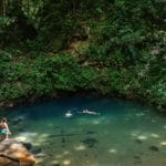 Swimmers floating in cool blue waters of jungle pool in Belize